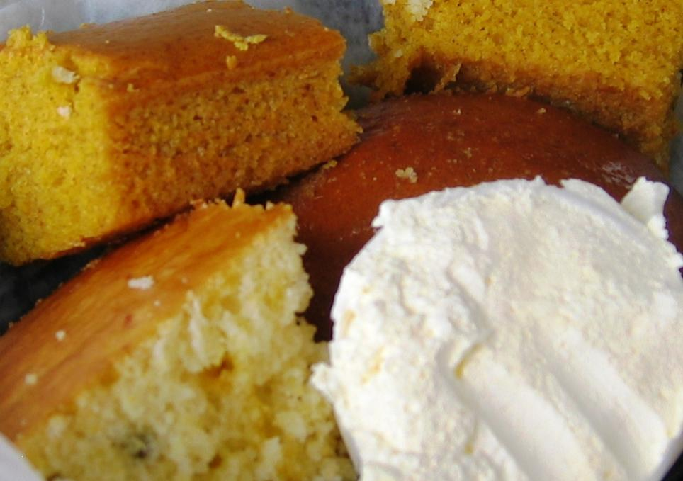 The bread basket holds an assortment of sweet corn bread squares, rolls,and spiced pumpkin bread.