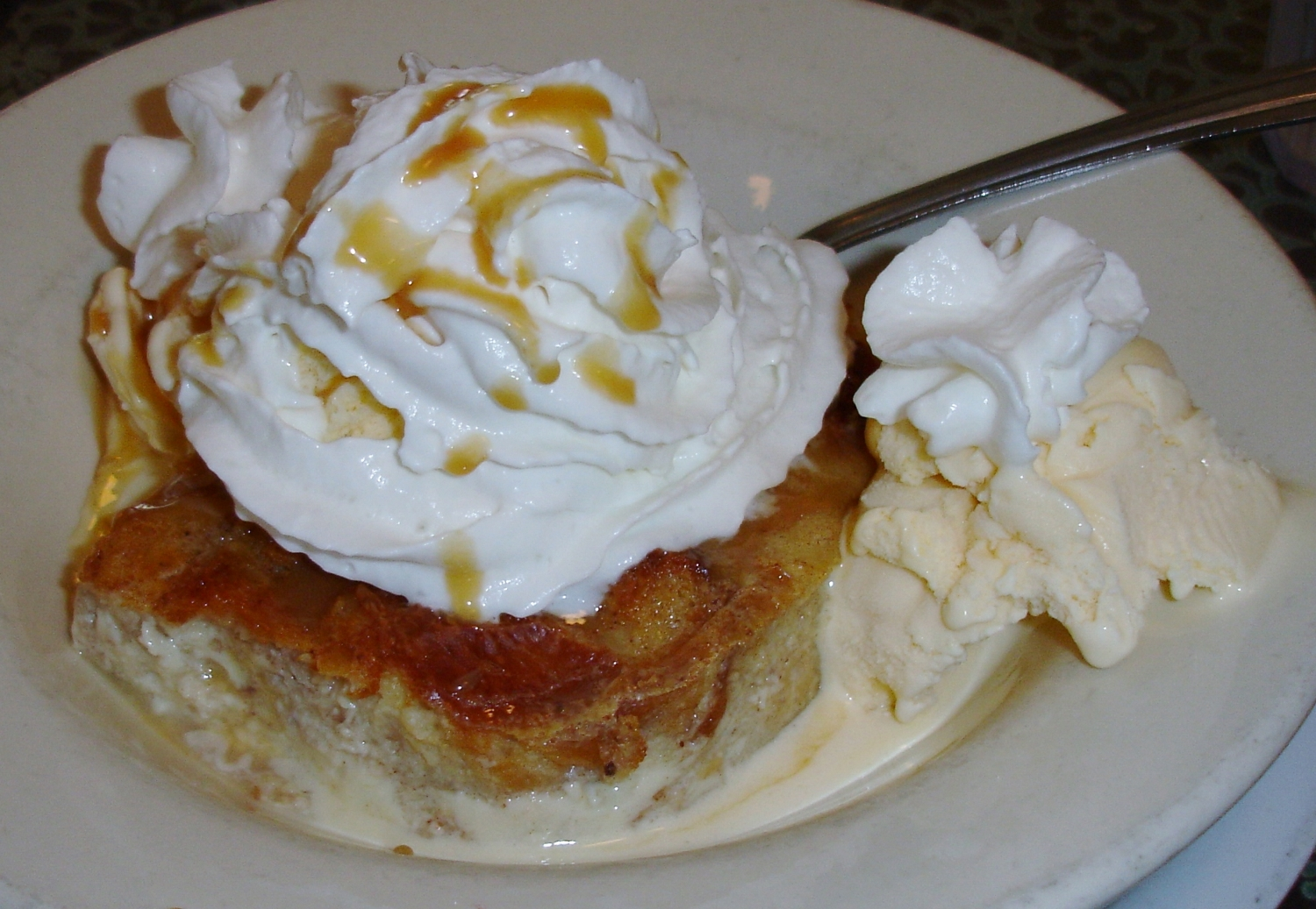 Ultimate Bread Pudding ups the ante with maple-candied pecans, ice cream, whipped cream, and caramel drizzle.