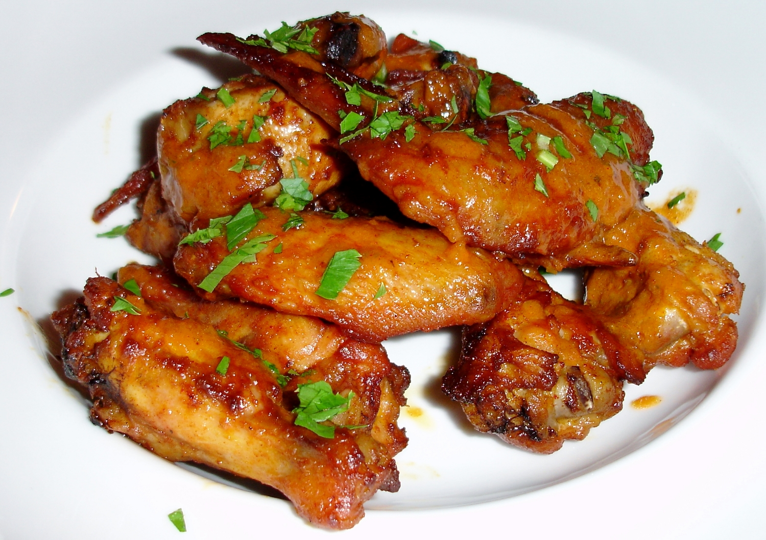 Chicken wings cooked in chicken fat, dressed with hot sauce, sprinkled with minced celery leaves