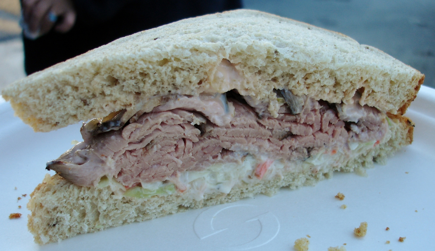 Have a sandwich made for you at the deli counter. This one features roast beef, cole slaw,and  Russian dressing on multi-grain bread.
