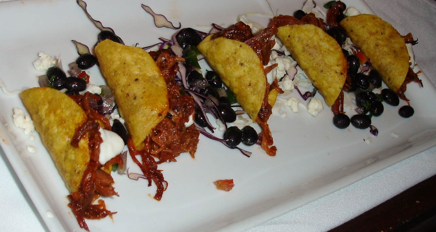 House Smoked Pulled Pork Tacos, served with black bean salsa, queso fresco, pico slaw, and cilantro creme fraiche