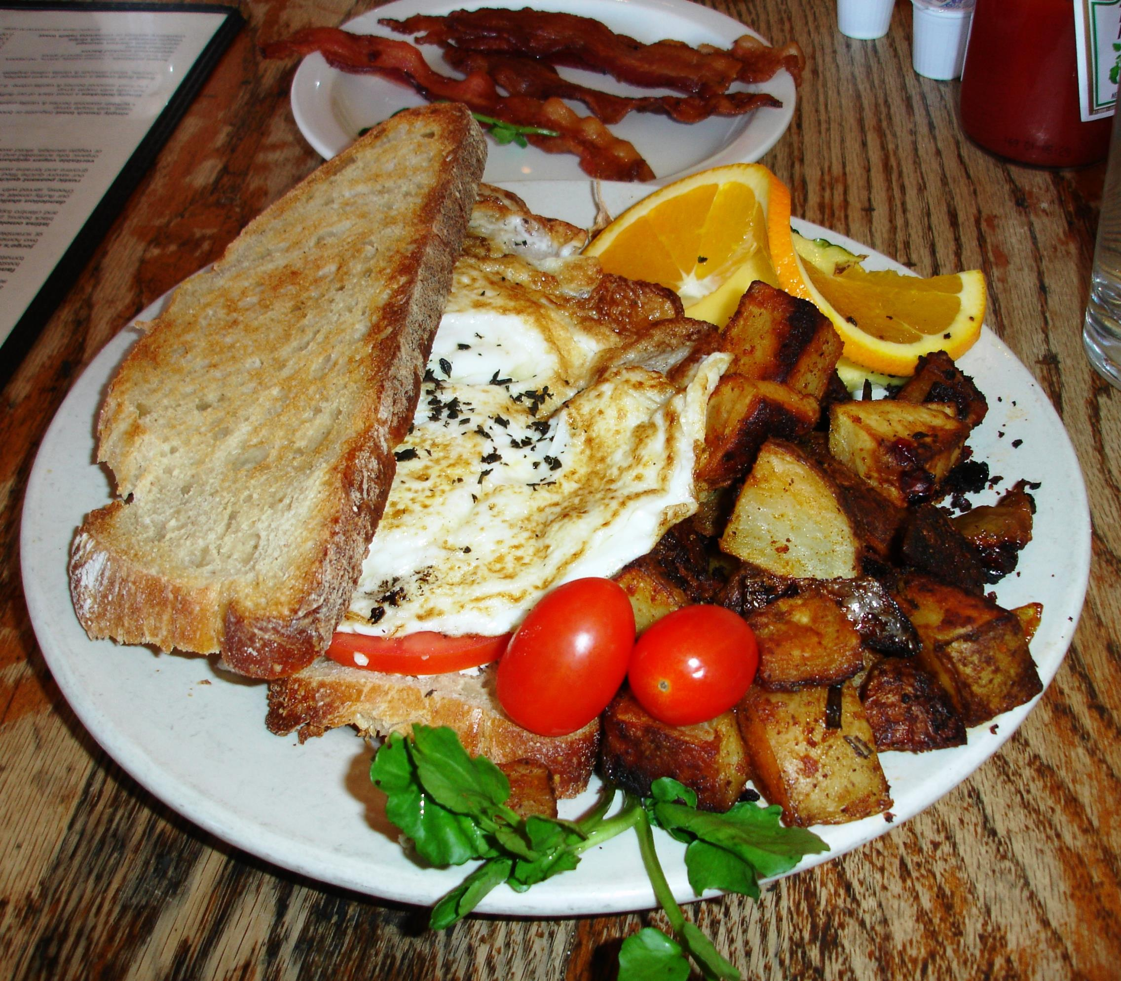Fannie's Killer Fried Egg Sandwich is a showstopper of over-medium eggs and gorgonzola, with applewood-smoked bacon, tomatoes, and fresh thyme, on toasted sourdough. M. Henry's excellent house potatoes are served alongside.