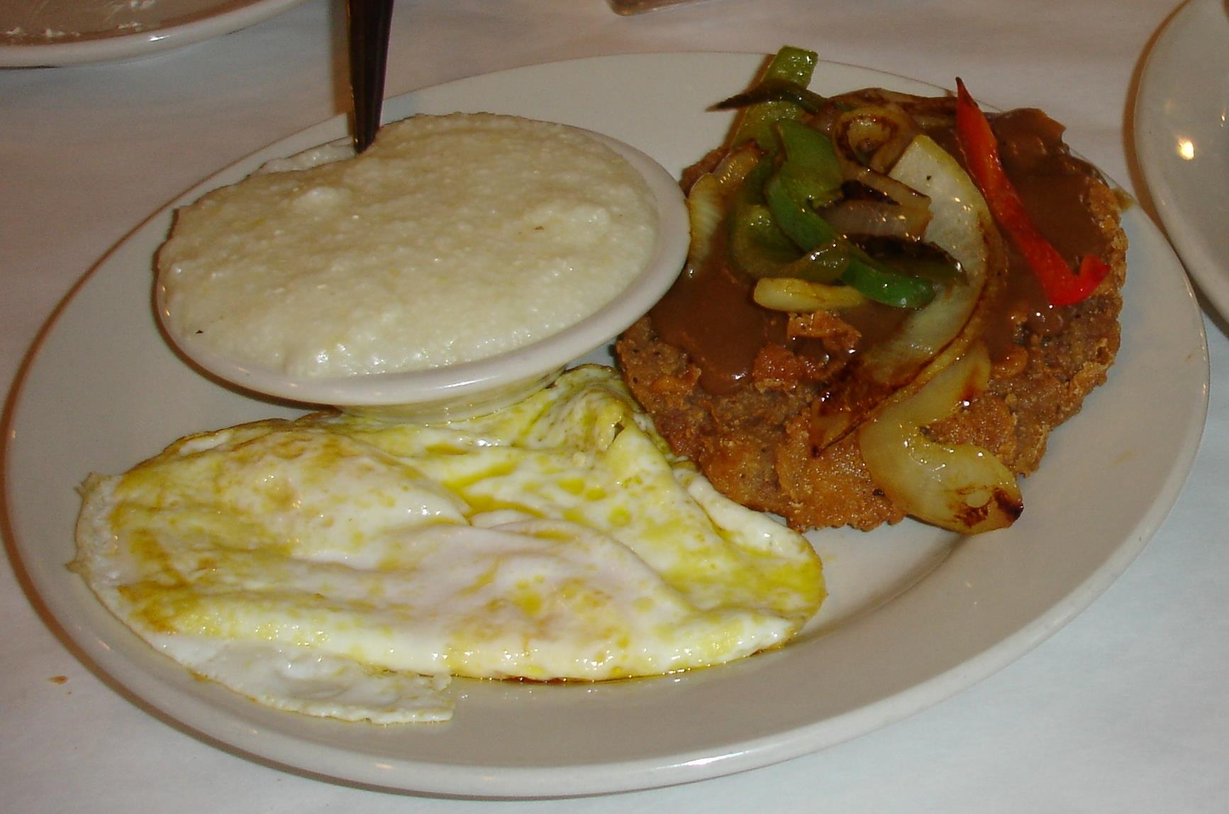 A Down South Breakfast includes country-fried steak, two eggs, grits, and (not-visible) two pancakes with syrup and butter.