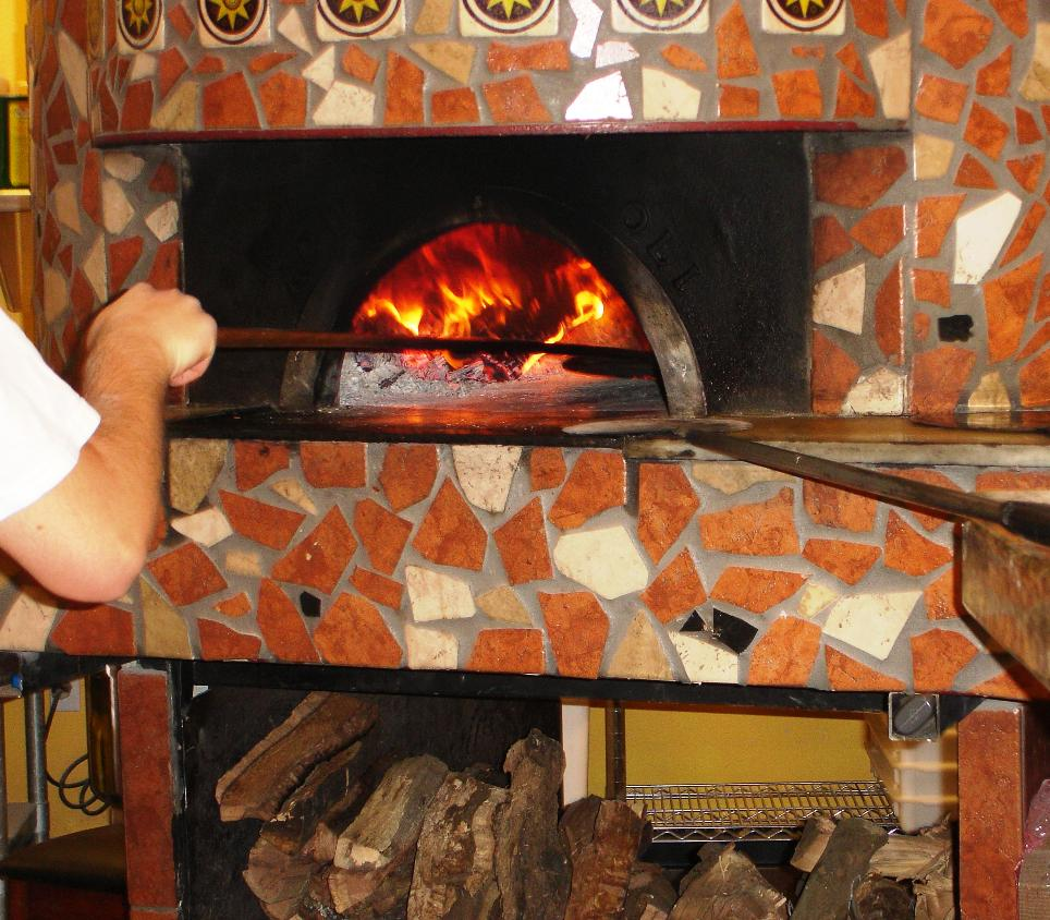 The pizzaiolo is sliding a pie into the wood-fired oven.