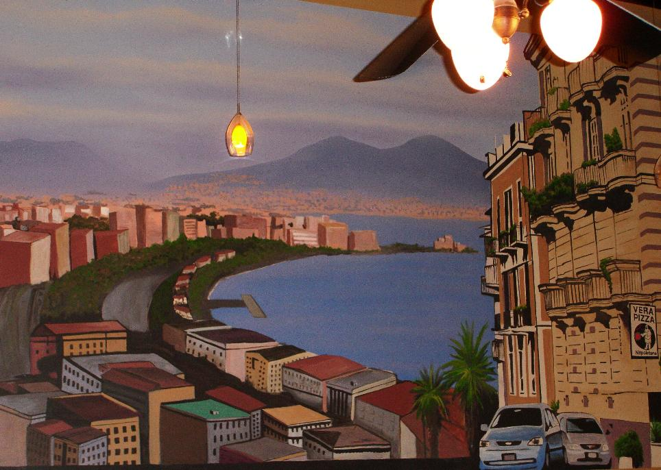 The painted mural is a waterfront scene of the spiritual home of pizzaioli everywhere, Napoli.