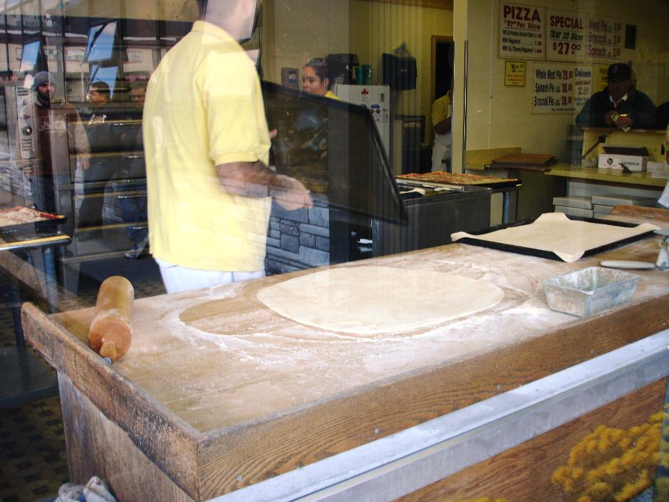The dough is rolled out and then stretched to fit a sheet pan. Ladles of tomato sauce are spread across the surface, then the pans are put in the oven to partially bake before being removed for the sprinkle of cheese, and any additional requested toppings. They then receive their final baking.