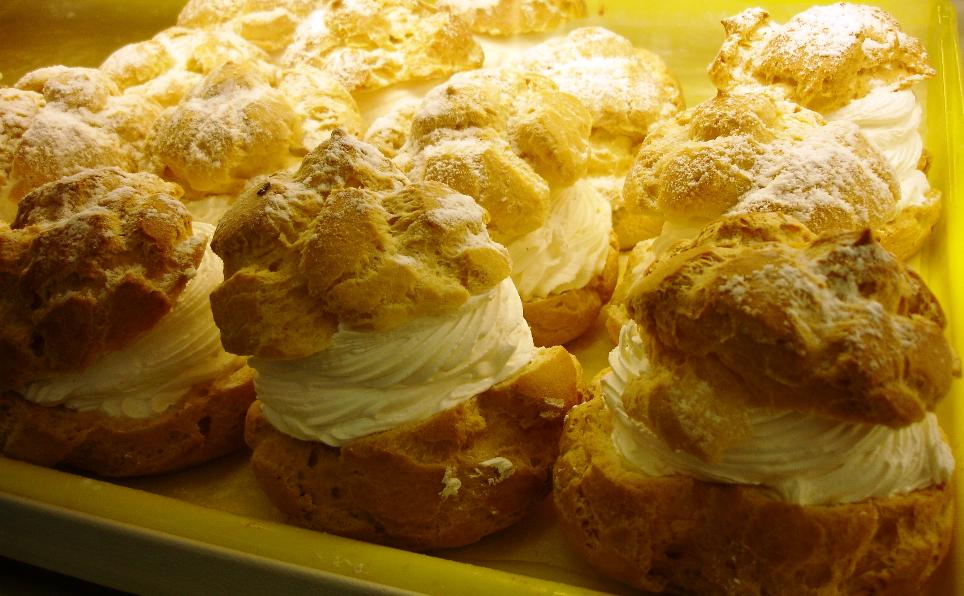 A tray of cream puffs arrayed in the bakery case