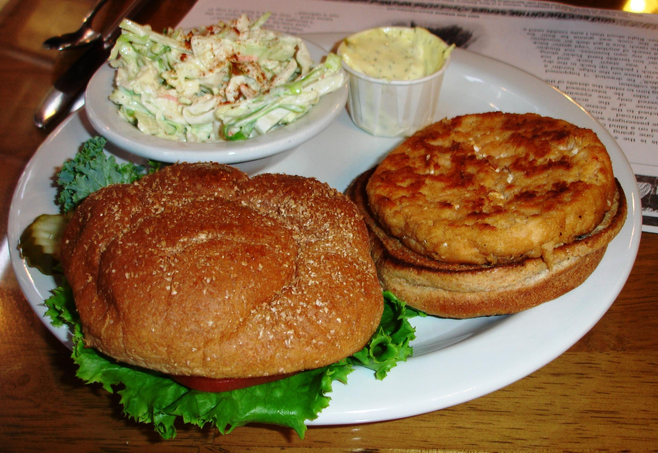 A grilled salmon burger arrives on a multi-grain bun with tartar sauce and, in this instance, coleslaw.