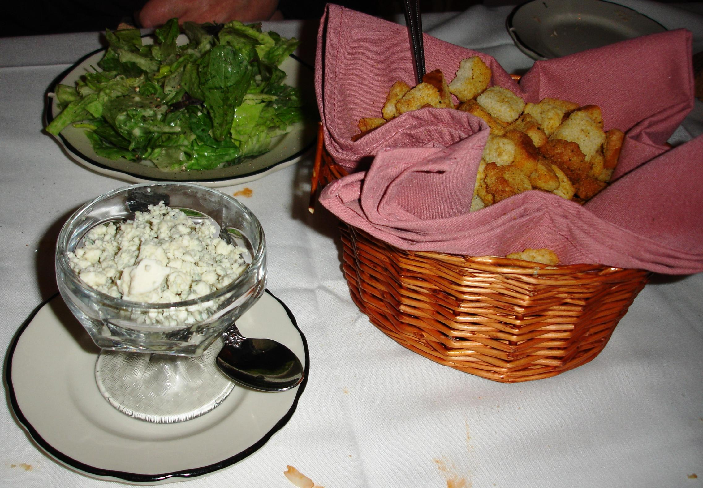 Salad is accompanied by a basket of house croutons and a dish of very creamy and mild blue cheese.