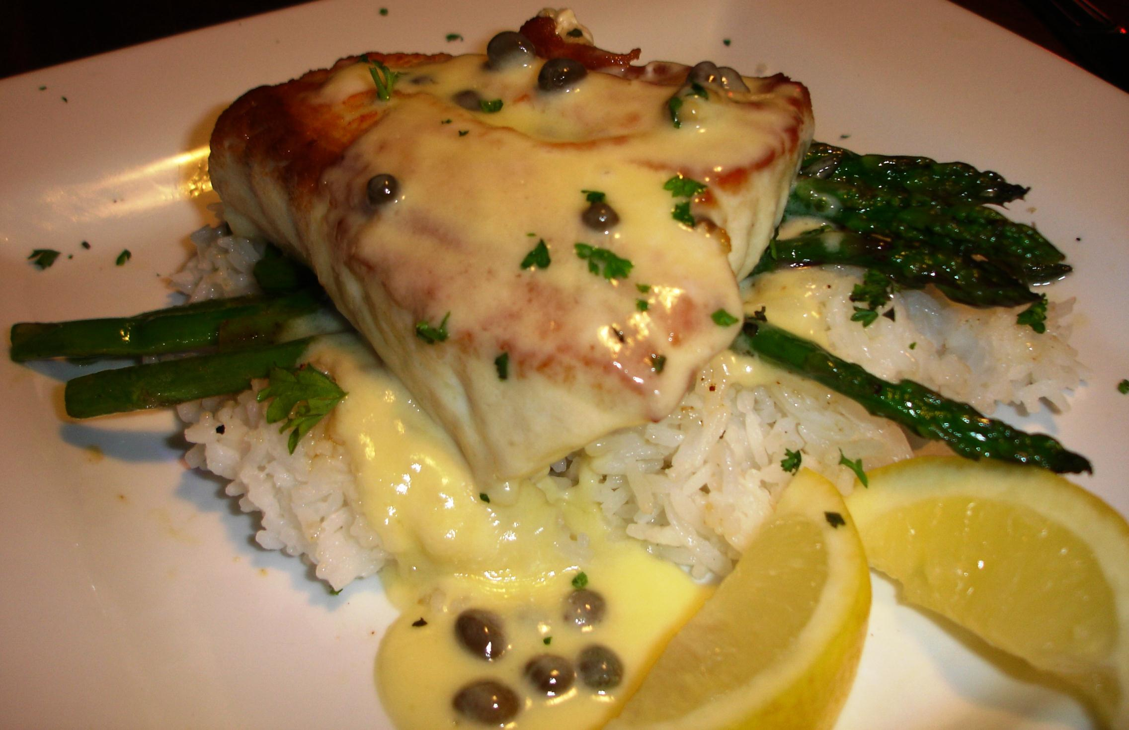 Halibut piccata is served over jasmine rice and in-season vegetables with a butter and caper sauce. The halibut is moist, meaty, and utterly fresh.
