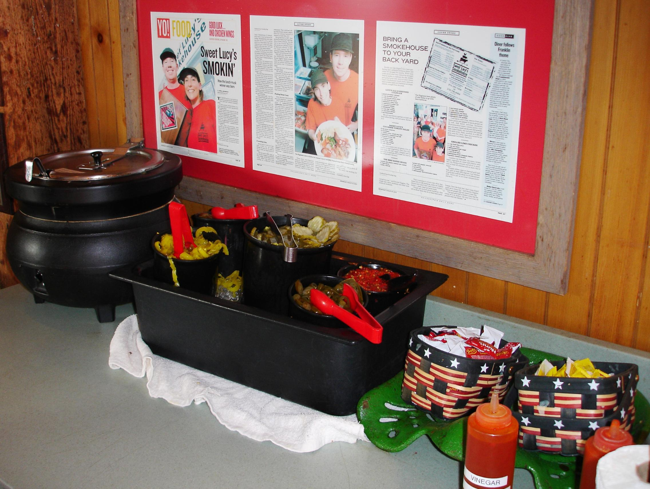 Barbecue sauce is kept warm at the condiments table.