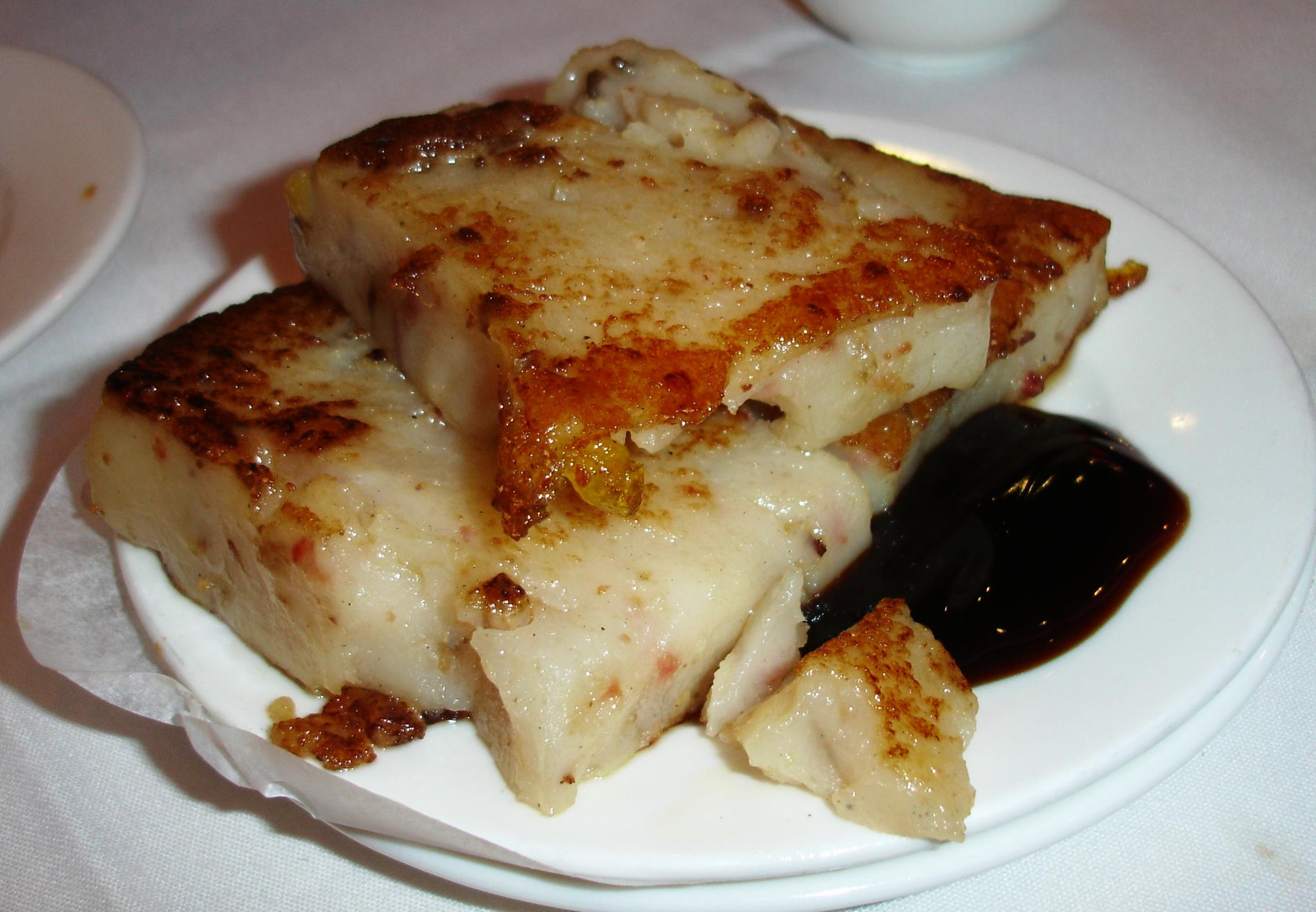 One of our favorite dim sum items anywhere is turnip cake, here called radish cake. A slice is cut from a starchy rice flour block that includes daikon radish and often bits of meat or seafood. The slice is pan-fried and served with sauce.
