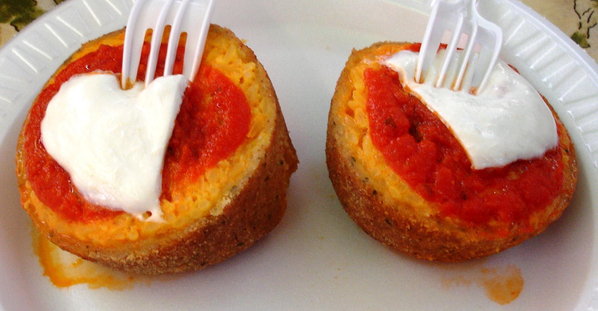 Arancini are fried rice balls, here garnished with tomato sauce and fresh mozzarella. They make a terrific snack.