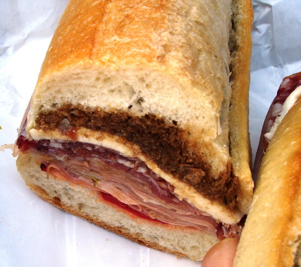 This hero contains imported Italian mortadella, a Tuscan-style fennel salami called finochiona, fresh mozzarella, and roasted peppers. The dark liquid soaking into the top of the roll is oil & balsamic vinegar. On this particular combo, in the future, we'd skip the balsamic.